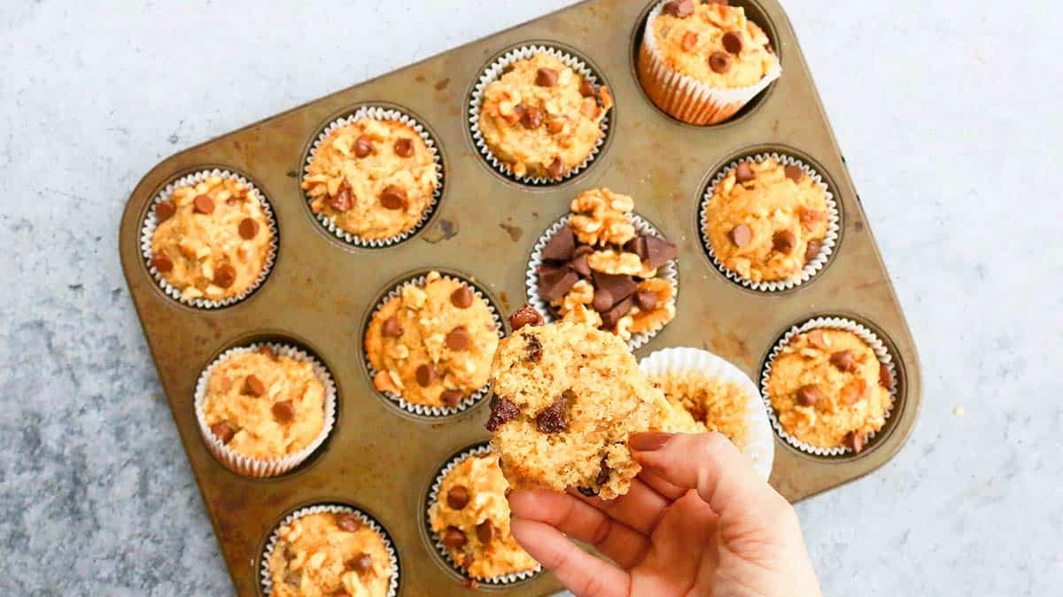 a hand holding a split banana muffin above a muffin pan filled with the same