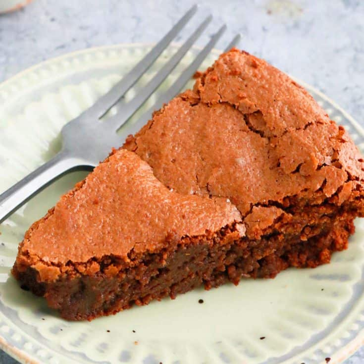 sliced almond flour chocolate cake placed on a small green plate with a fork on the side