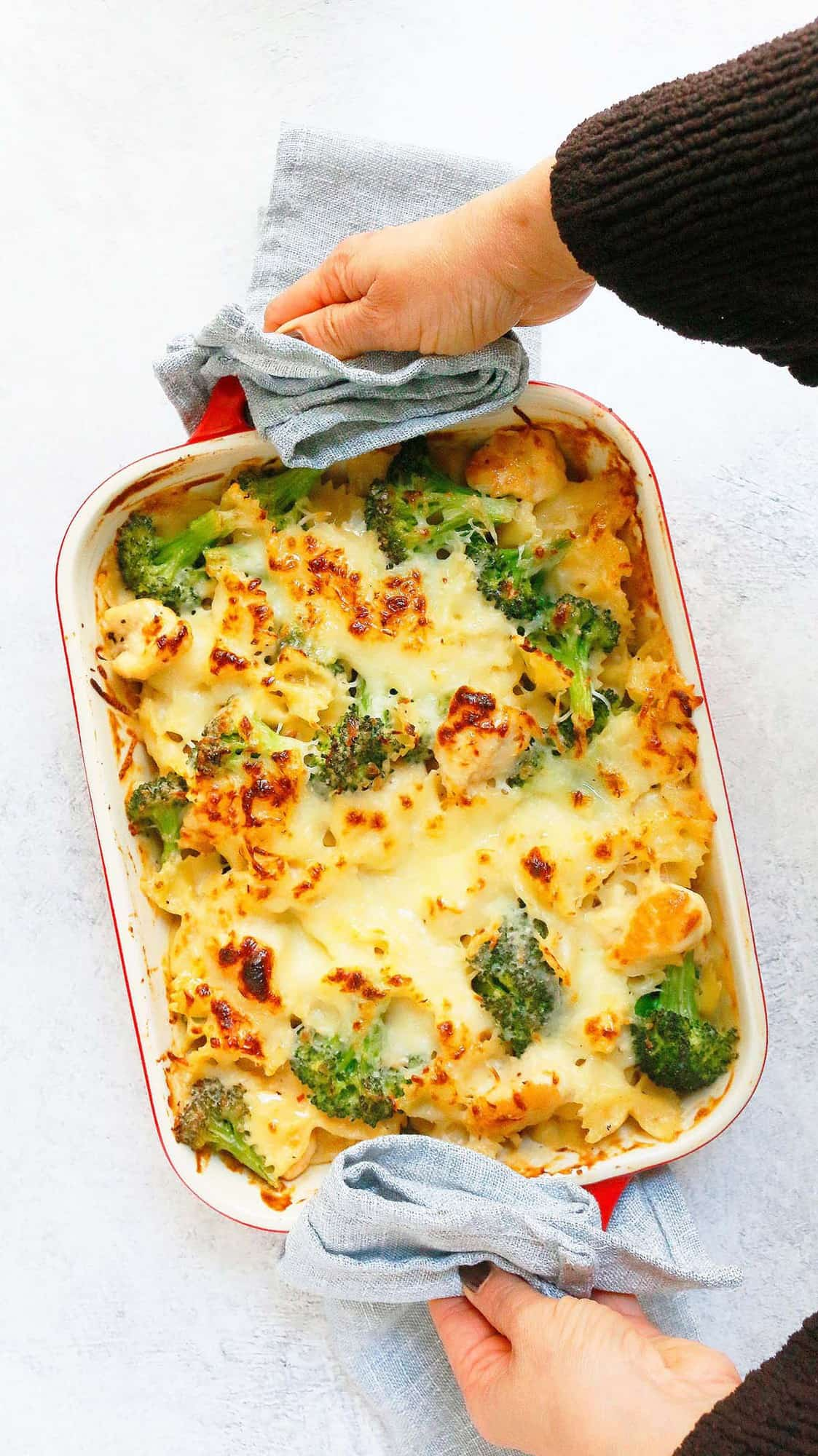 two hands holding a hot chicken pasta broccoli bake in a red pan with grey towels.