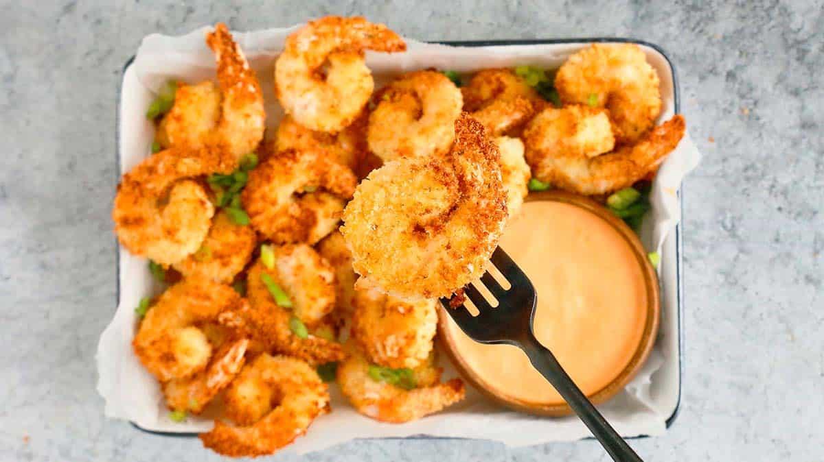 black fork holding a breaded shrimp above a platter filled with the same
