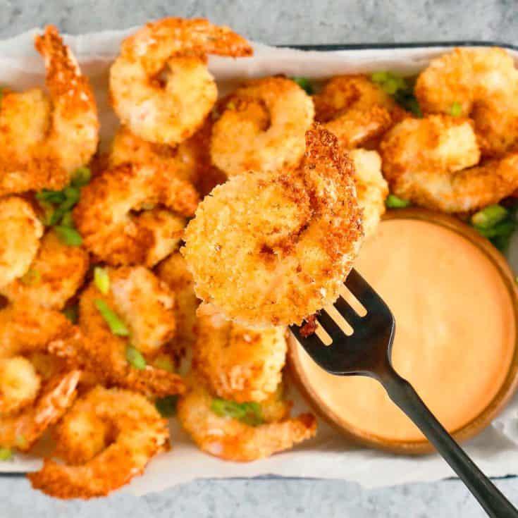 fork holding a crispy shrimp above a platter filled with more shrimp