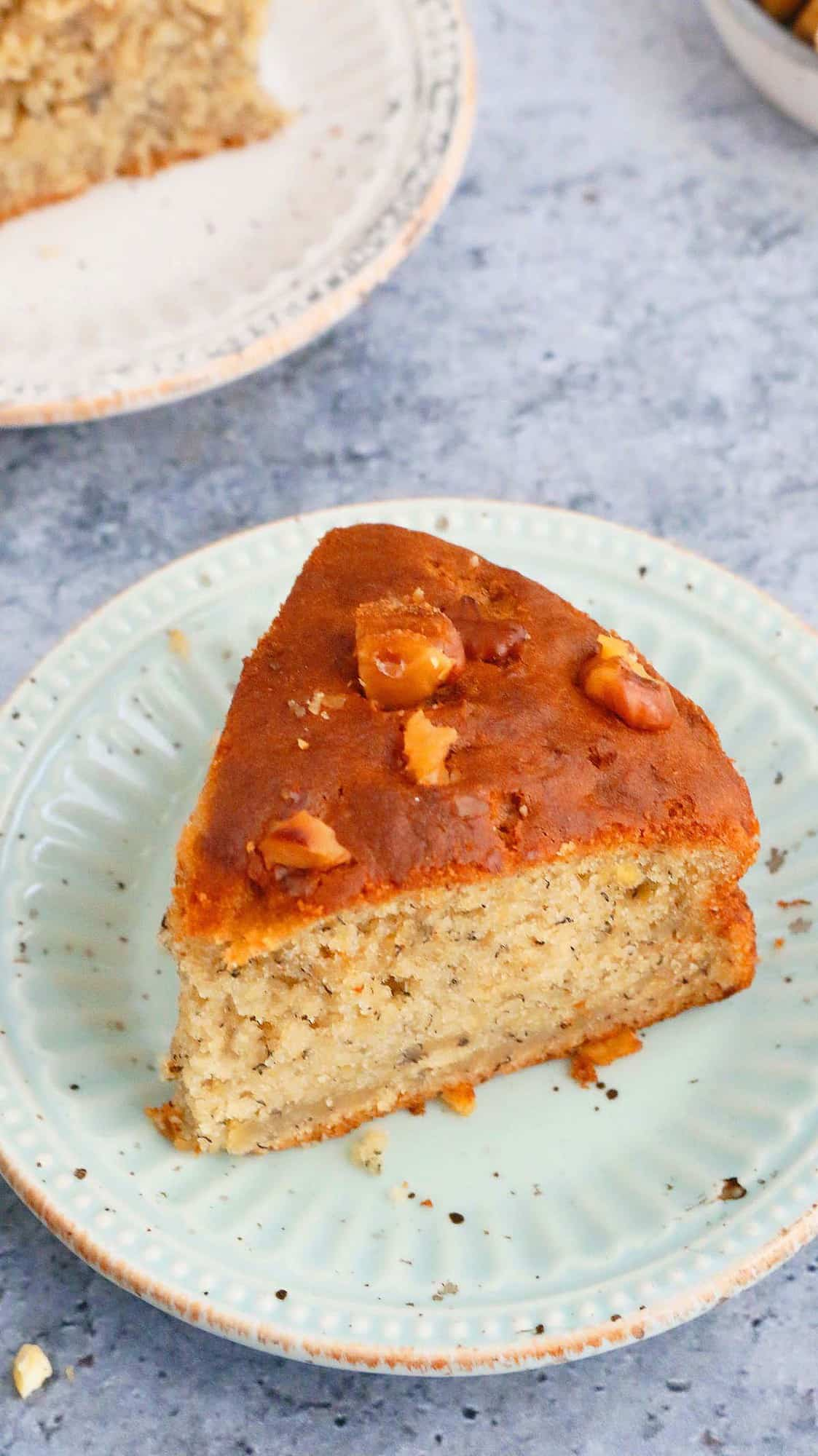 a slice of banana cake with walnuts on top