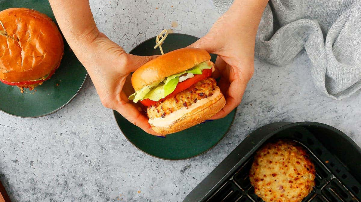 two hands holding a ground chicken burger
