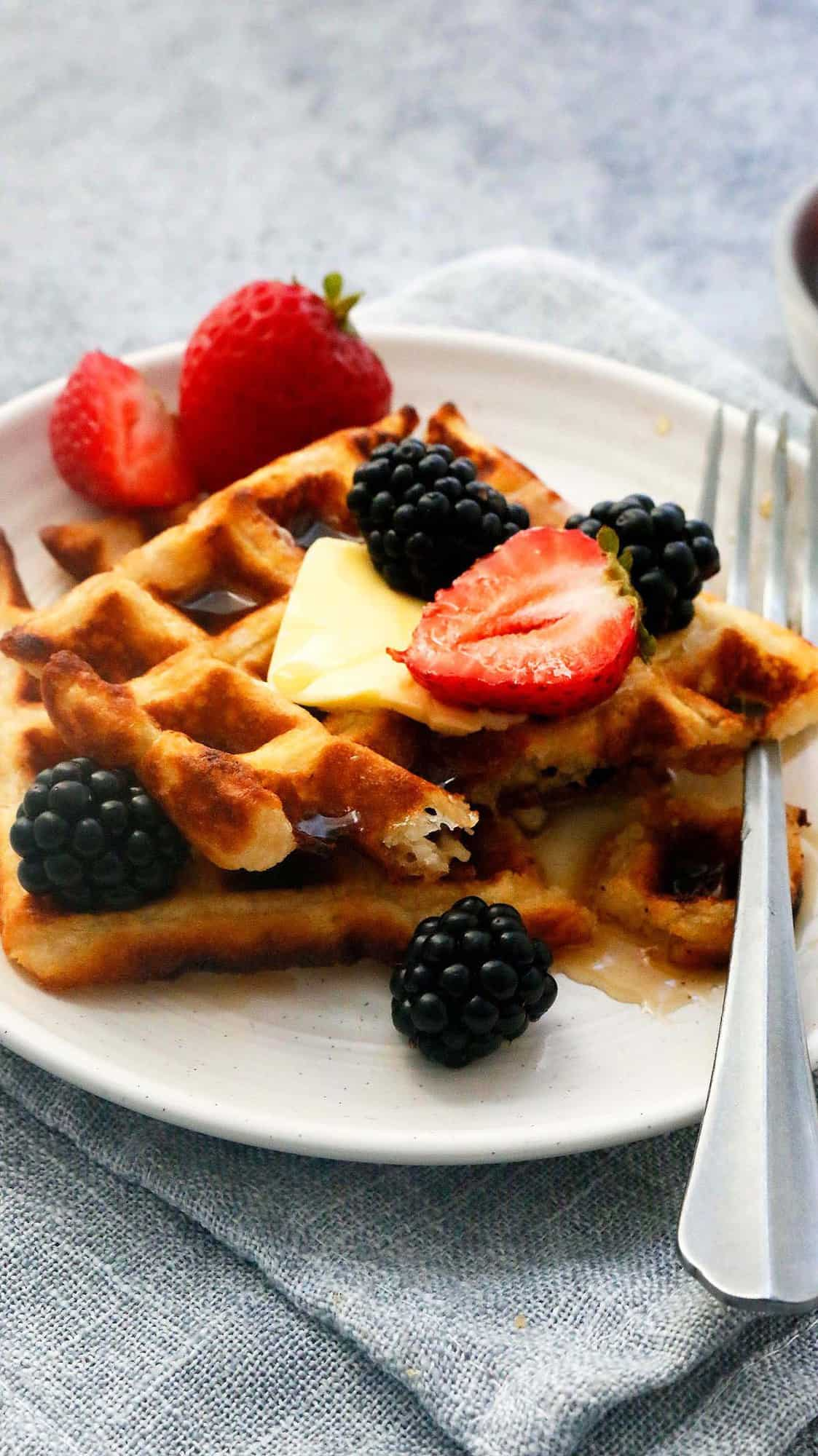 eggless waffles served on a white plate along with a fork