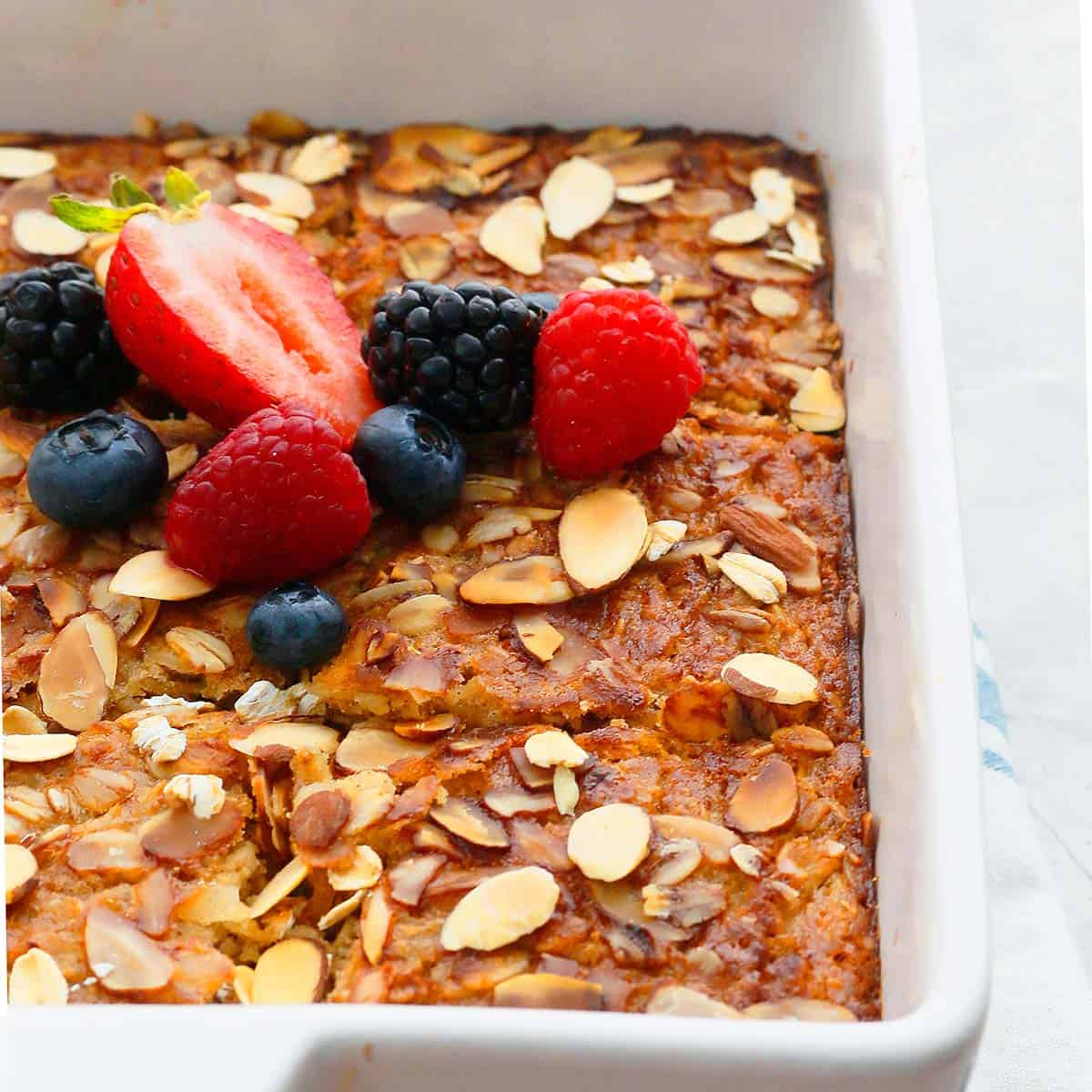 gluten free baked oatmeal with bananas topped with fresh fruits.