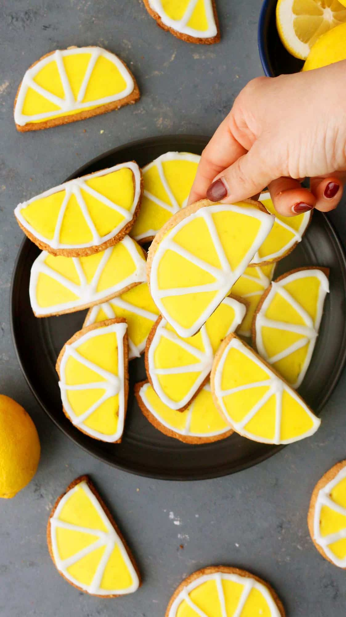 hand holding a almond lemon cookie above a platter filled with the same